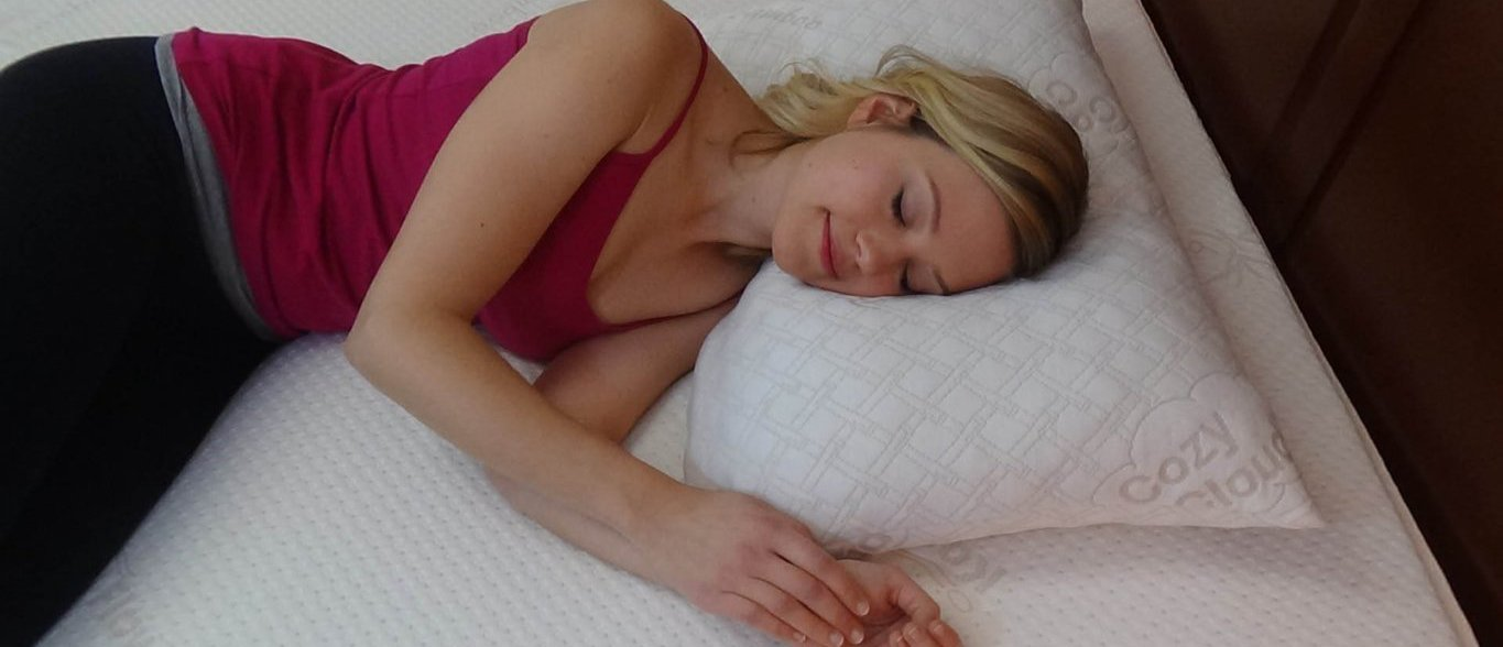 Side sleeper lying on a queen-sized CozyCloud contouring memory foam pillow with a bamboo cover